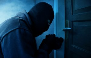 Masked thief breaking into a home